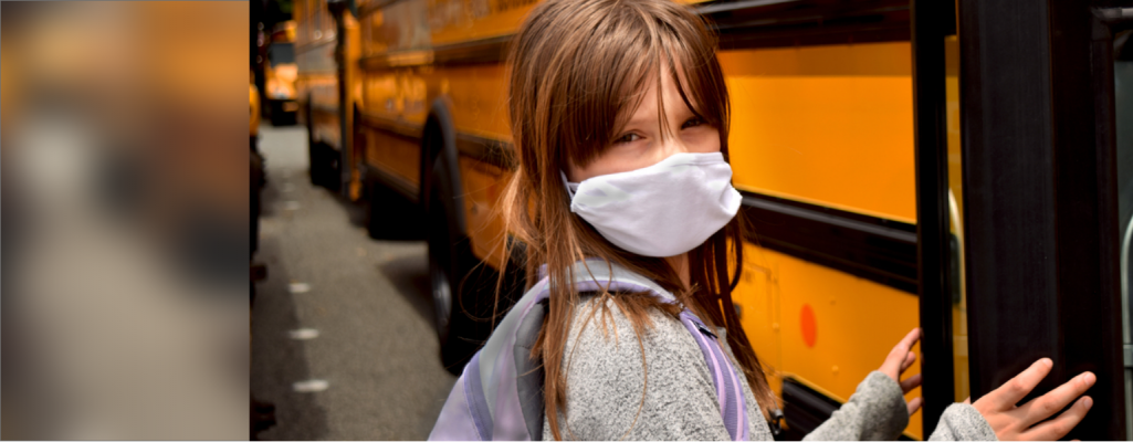 Student wearing a mask beside a school bus