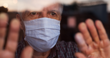 A senior man with surgical mask with hands touching window